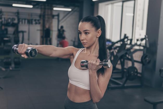 Mujer sana joven que disfruta ejercitándose con pesas en el gimnasio.