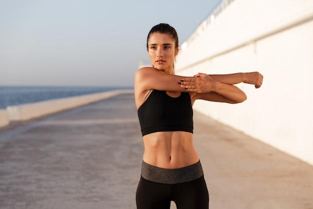 Mujer sana joven que estira y que entrena cerca del mar