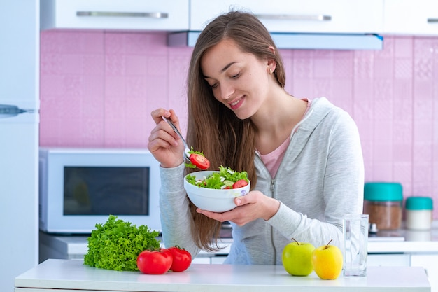 Mujer sana joven en ropa deportiva que come la ensalada de las verduras frescas en casa en cocina. dieta orgánica equilibrada y alimentación saludable.