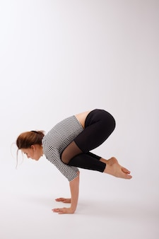 Mujer sana en polainas deportivas negras haciendo asanas bakasana sobre un fondo blanco aislado de fondo. dia de yoga