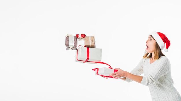 Mujer en santa sombrero cayendo cajas de regalo