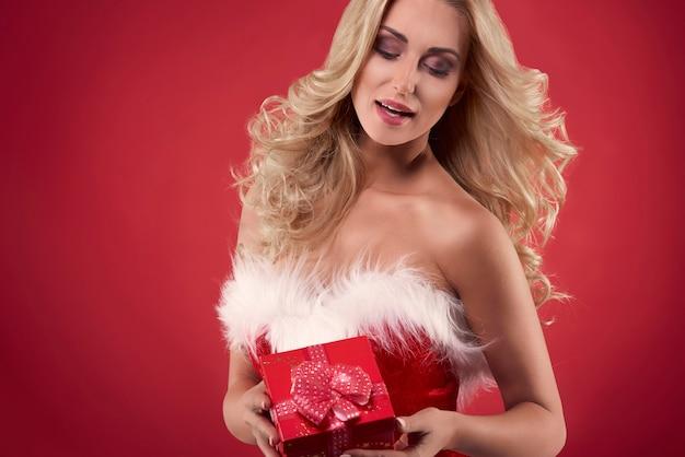 Mujer santa sosteniendo una caja de regalo roja
