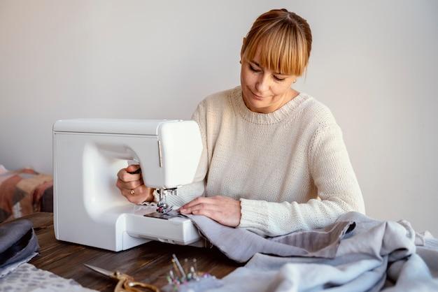 Mujer de sastre con máquina de coser