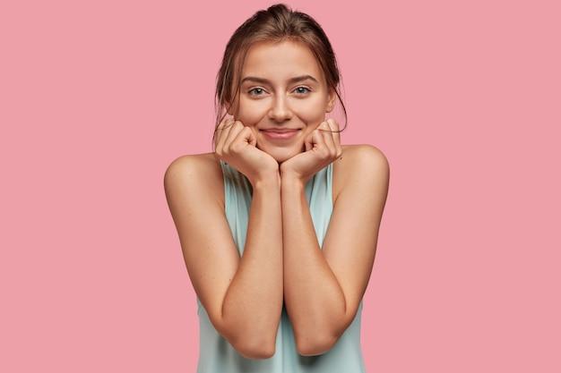 Mujer satisfecha con expresión encantada, mantiene la mano debajo de la barbilla, tiene una piel sana, ojos verdes