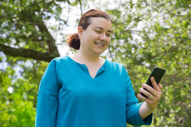 Mujer satisfecha positiva con teléfono móvil