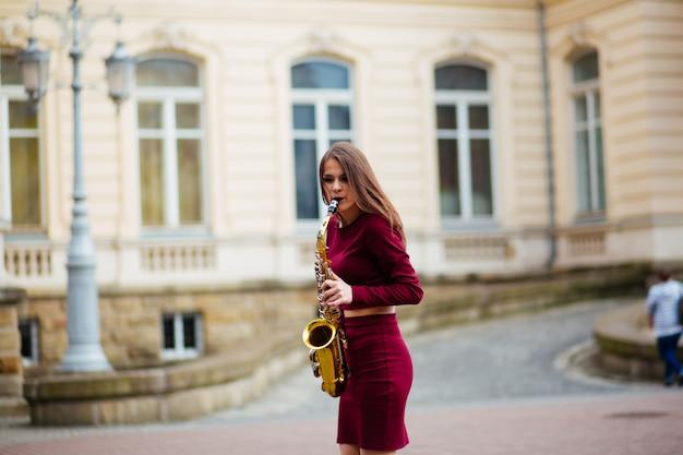 Mujer saxofonista tocando el saxofón en la calle