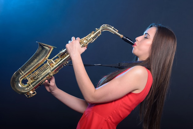 Mujer saxofonista en vestido rojo