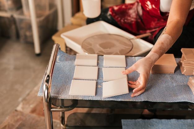 Mujer secando los pequeños azulejos blancos en taller.