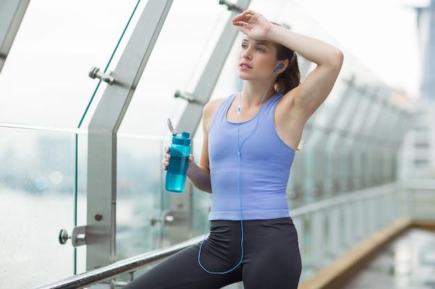 Mujer secándose el sudor de la frente mientras sujeta una botella de agua