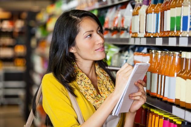 Mujer en la sección de comestibles escribiendo en el bloc de notas