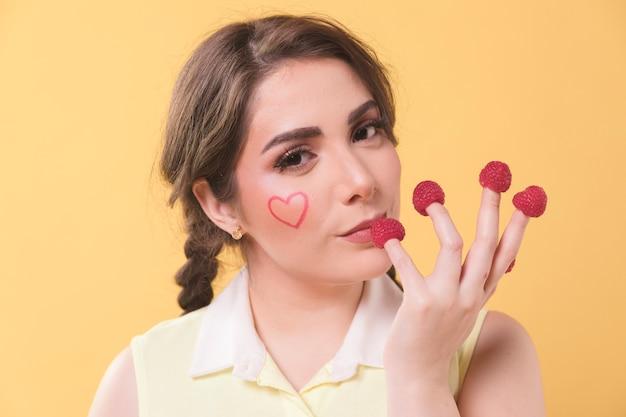 Mujer seductora con frambuesas en la punta de los dedos