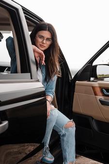 Mujer seductora con gafas viajando sola en coche