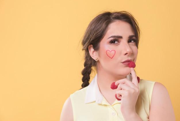 Mujer seductora posando con dedos de frambuesa
