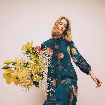 Mujer segura atractiva en vestido con ramo de flores frescas