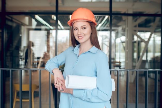 Mujer segura de casco de seguridad con esquemas
