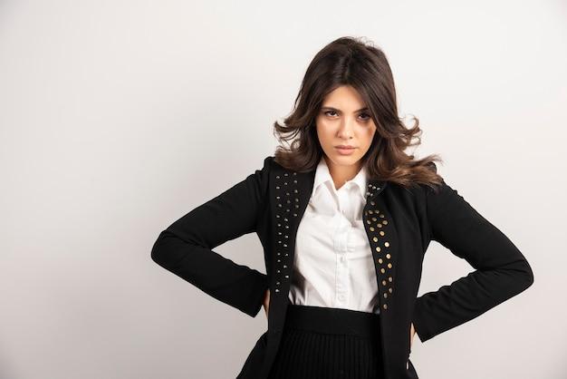 Mujer segura de chaqueta negra sosteniendo su cintura