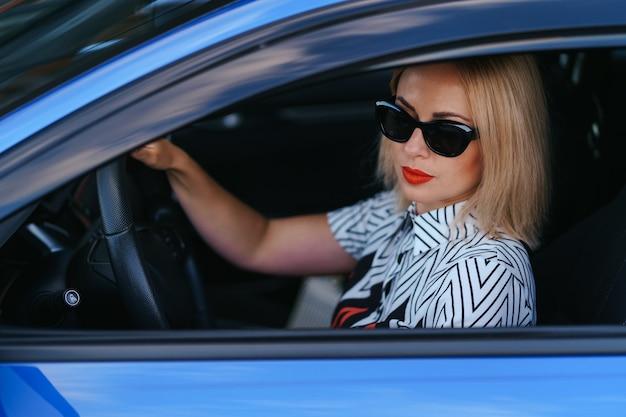 Mujer segura y hermosa en gafas de sol. vista trasera de la atractiva mujer joven en ropa casual conduciendo un coche