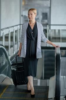 Mujer segura con maleta en escaleras mecánicas del aeropuerto