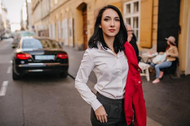 Mujer segura de pelo negro posando en la calle con coche en la pared