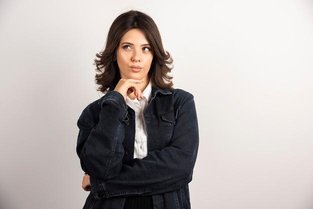 Mujer segura de pie de chaqueta de mezclilla en blanco.