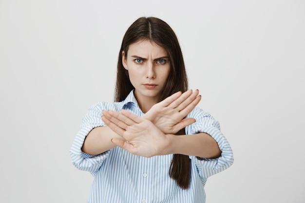 Mujer segura seria mostrar señal de stop, gesto cruzado