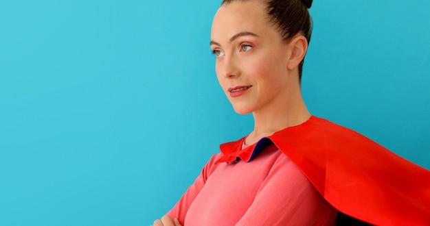 Mujer segura de sí misma en capa roja, superhéroe