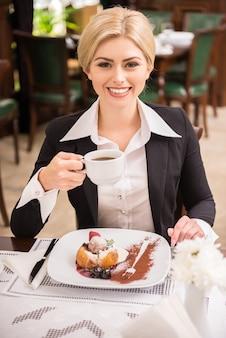 Mujer segura en traje disfrutando de café en almuerzo de negocios.