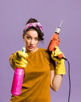 Mujer segura usando el taladro y el aerosol