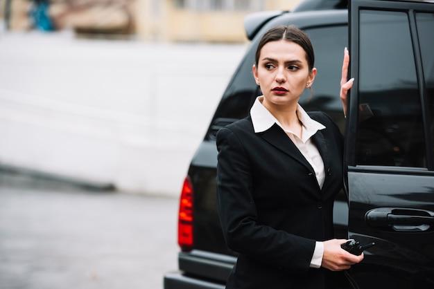 Mujer de seguridad abriendo coche para cliente
