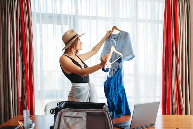 Mujer selecciona atuendos en la oficina, pensando en el viaje.