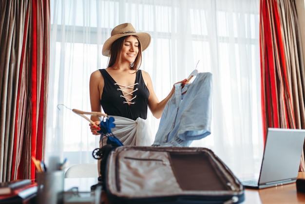 Mujer selecciona atuendos, pensando en viaje