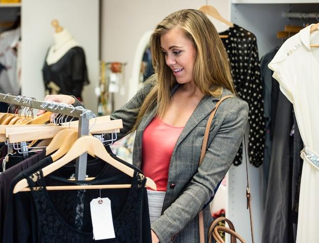 Mujer seleccionando un vestido mientras compra ropa