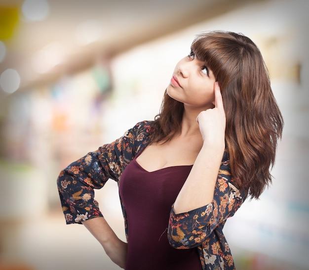 Mujer señalando con un dedo en la sien