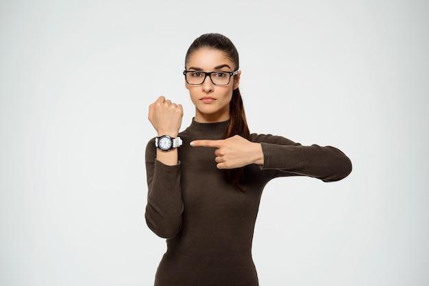 Mujer señalando reloj, el tiempo se acaba
