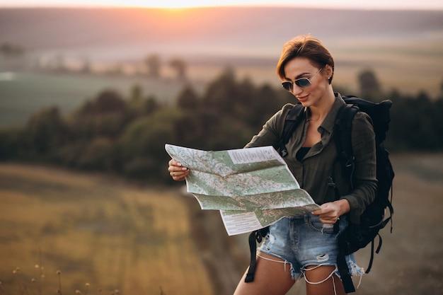 Mujer de senderismo en las montañas y mirando en el mapa