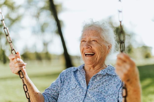 Mujer senior alegre en un columpio en un patio de recreo