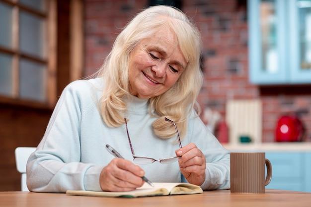 Mujer senior de ángulo bajo escribiendo en agenda
