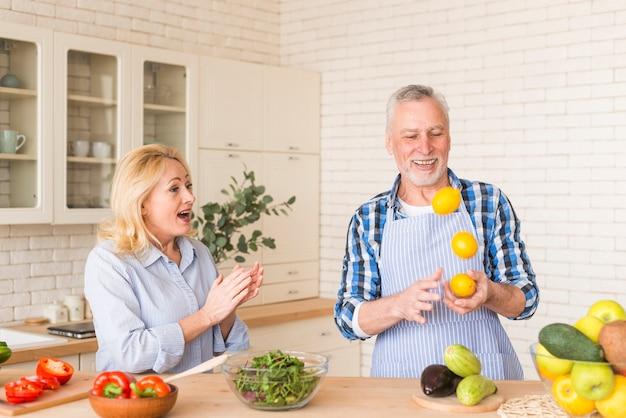 Mujer senior aplaudiendo mientras su esposo hace malabares con naranjas enteras en la cocina
