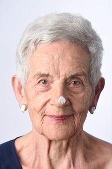 Mujer senior aplicando crema o crema hidratante en la cara