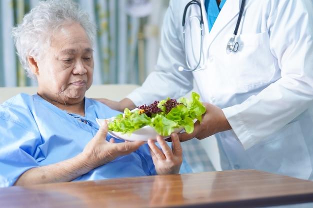 Mujer senior asiática comiendo ensalada