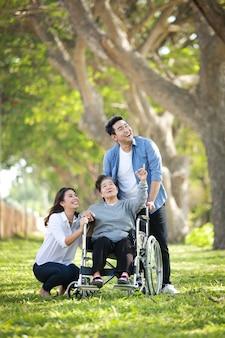 Mujer senior asiática sentada en la silla de ruedas con cara de sonrisa feliz de familia en el parque verde