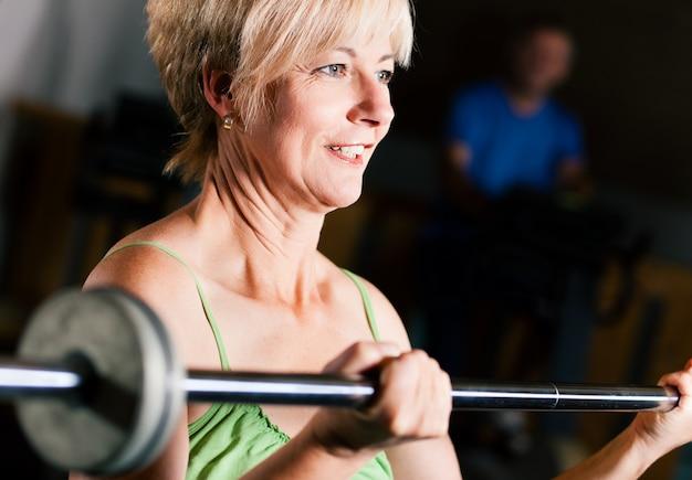 Mujer senior con barra en el gimnasio