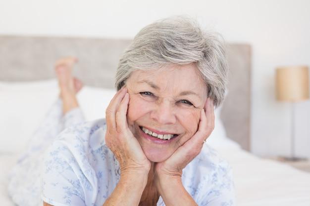 Mujer senior con la cabeza en las manos en la cama