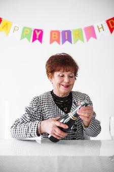 Mujer senior celebrando su cumpleaños en casa con pastel, globos y confeti