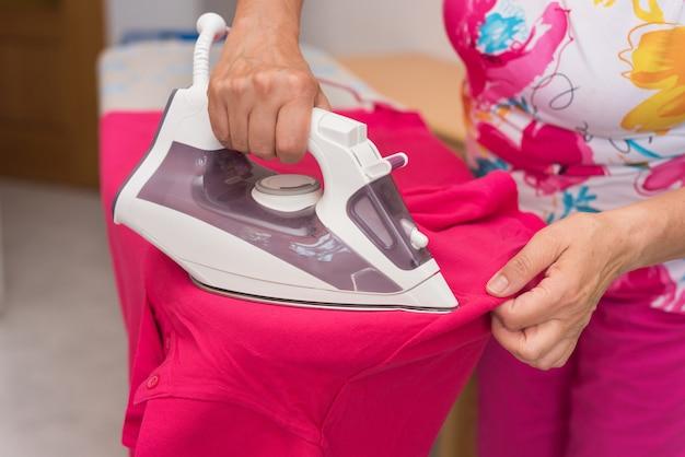 Mujer senior de cerca planchando ropa