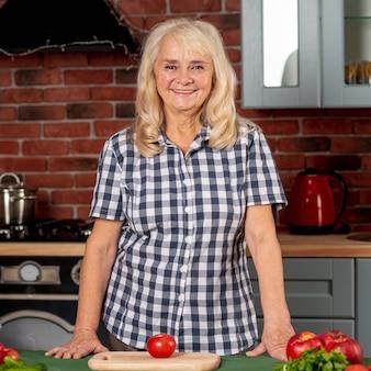 Mujer senior en cocina preparada para cocinar