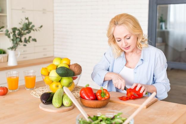 Mujer senior cortando el pimiento rojo con un cuchillo en la mesa de madera
