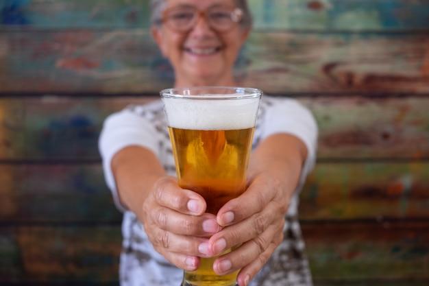 Mujer senior defocused sentada en una mesa de madera sosteniendo un vaso de cerveza rubia, mirando a la cámara sonriendo