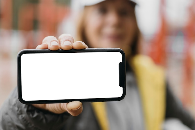 Mujer senior defocused sosteniendo smartphone al aire libre