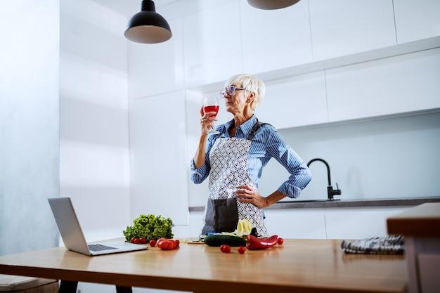 Mujer senior en delantal de pie en la cocina, bebiendo vino y preparando una cena saludable